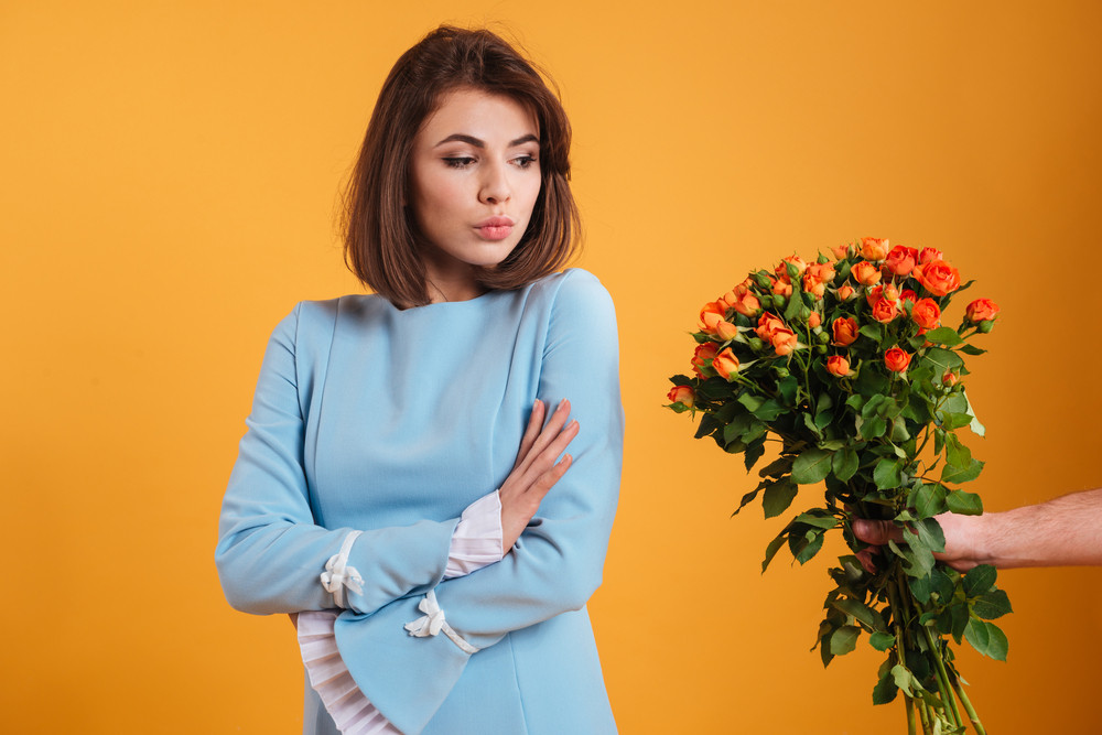 Angry offended young woman standing with arms crossed and receiving bouquet of flowers over yellow background