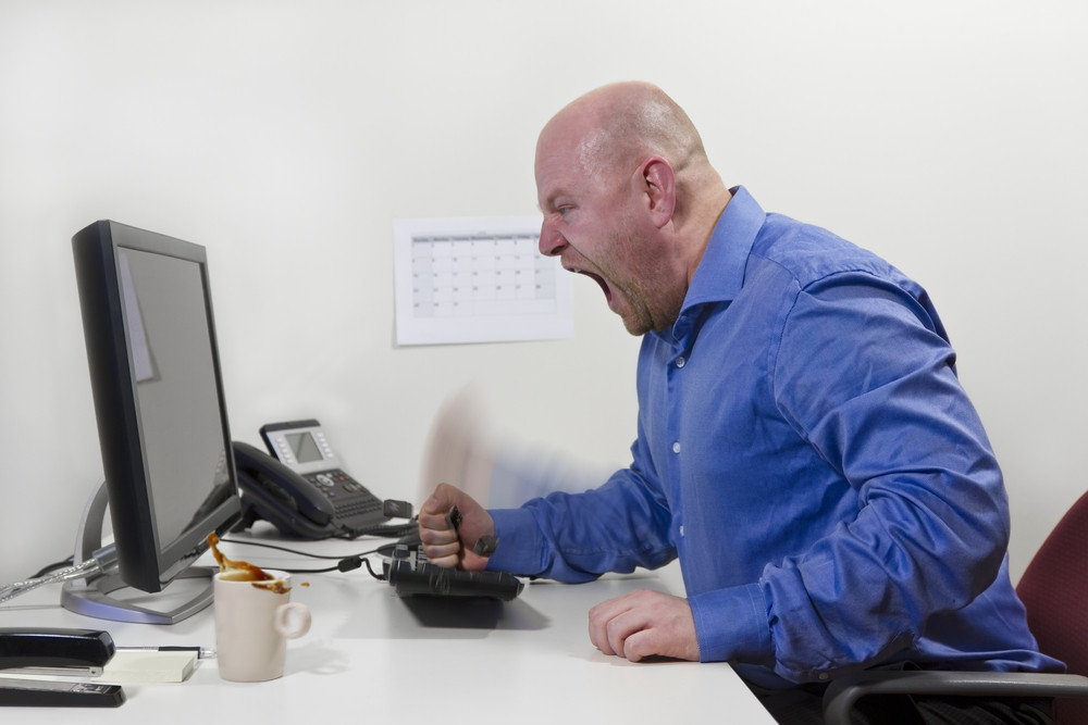 Angry office worker / businessman hit his computer keyboard. Keys and coffee in motion.