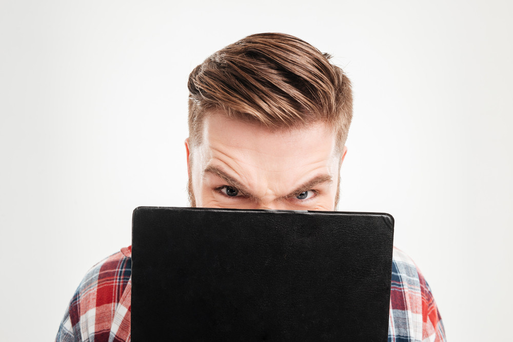 Angry young man covers his face with black folder isolated on a white background