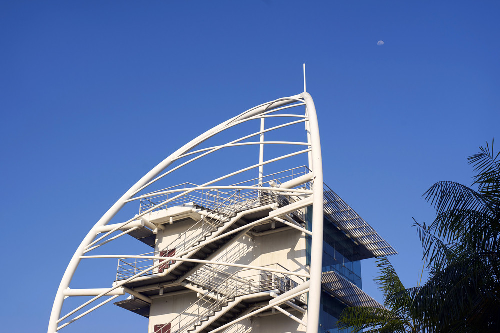 Architectural fragment of the white tower with a metal  staircase against the blue sky