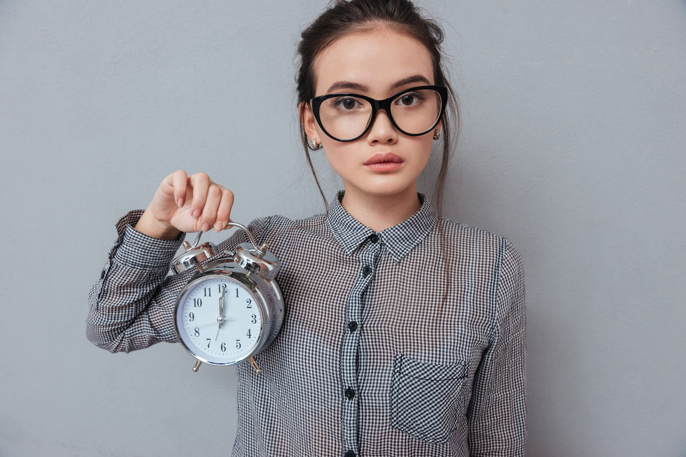 Asian cute woman in glasses and shirt holding clock and looking at camera. Isolated gray background