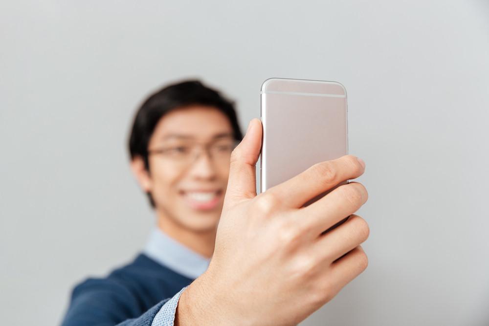 Asian man makes selfie. smiling