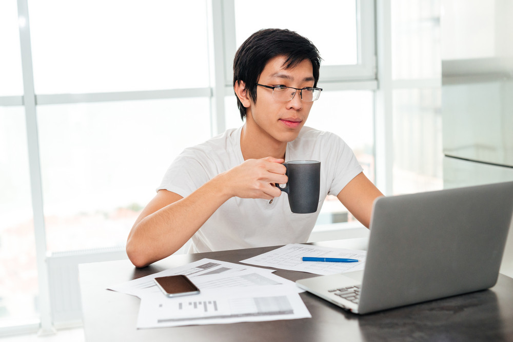 Asian man sits by the table with coffee and laptop