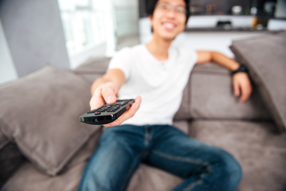 Asian man watching tv on sofa. front view
