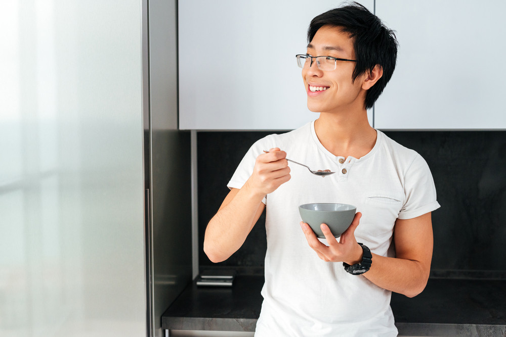 Asian man with cereal. in th kitchen. looking away