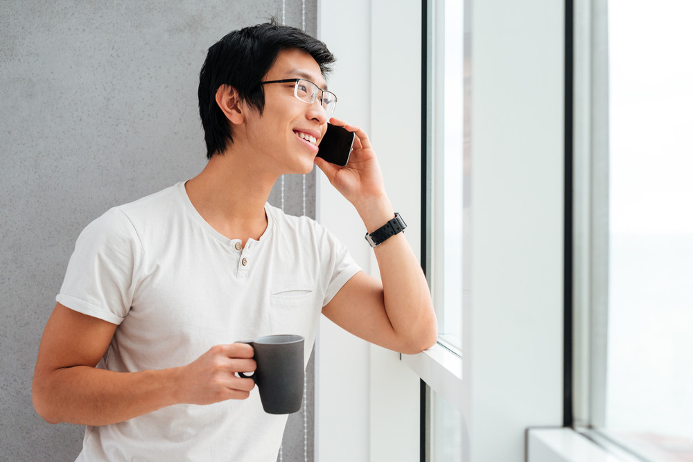 Asian man with coffee and phone near the window