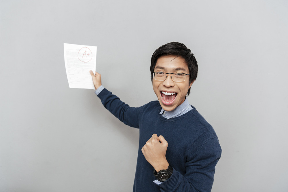 Asian student shows his work. looking at the camera. with glasses