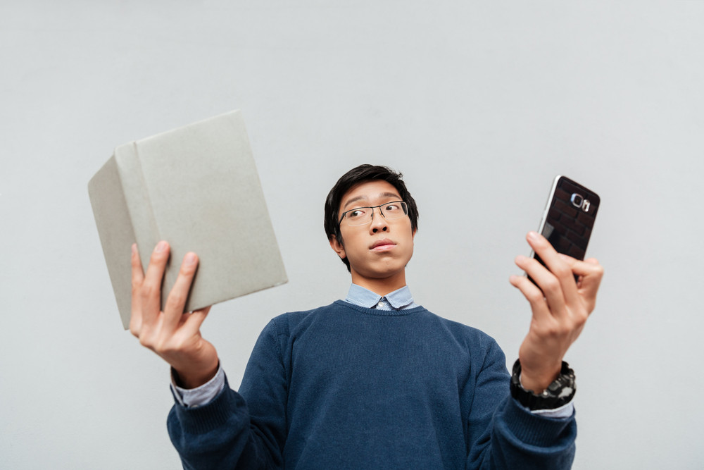 Asian student with book and phone.from below. surprised