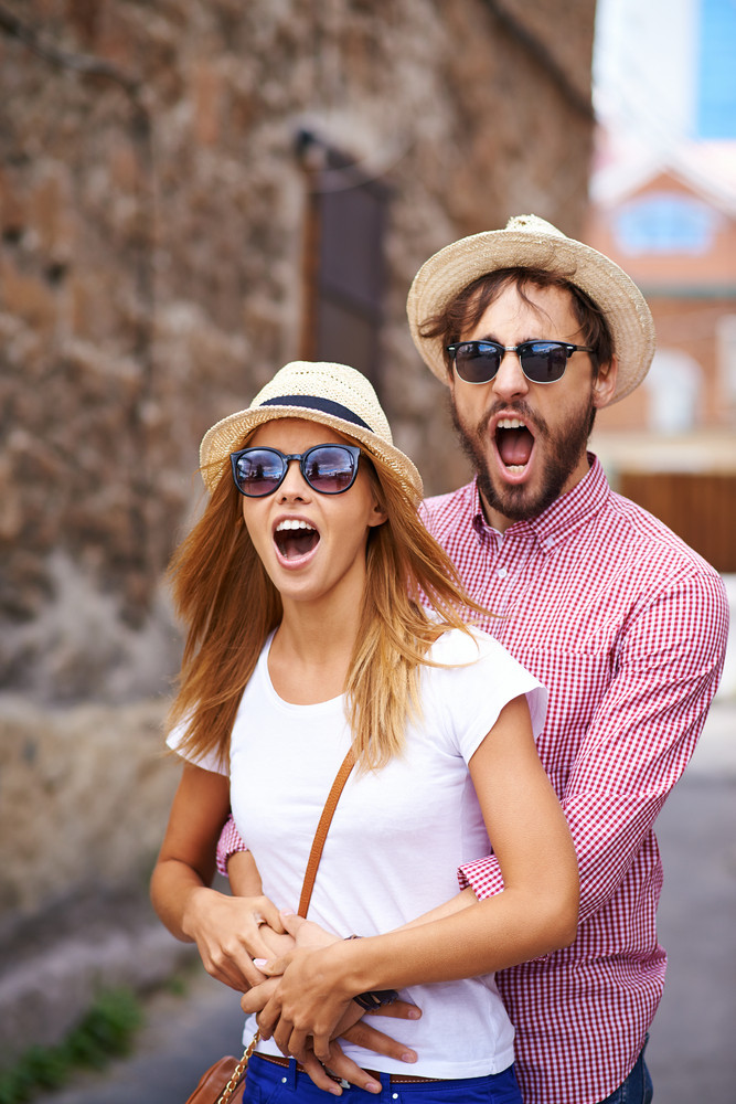 Astonished dates in hats and sunglasses