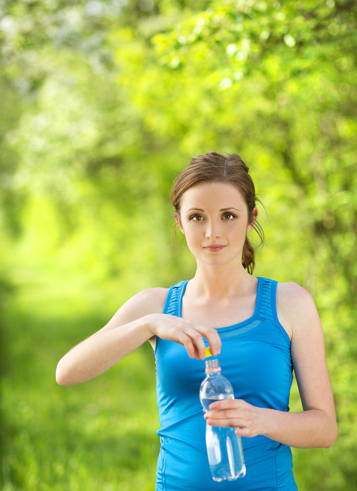 Athlete refreshing with a bottle of water during the outdoor exercise