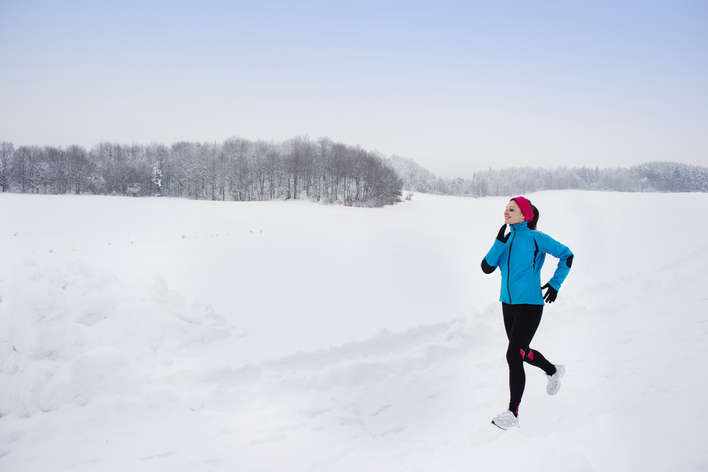 Athlete woman is running during winter training outside in cold snow weather.