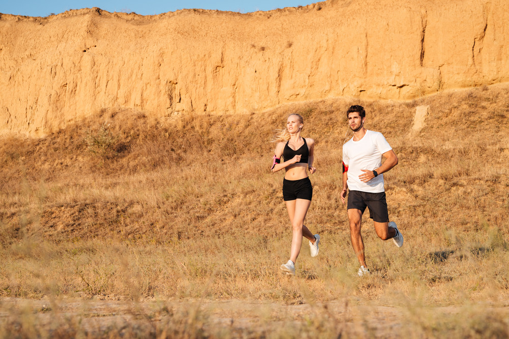 Athletic female runner and male fitness model running together outdoors