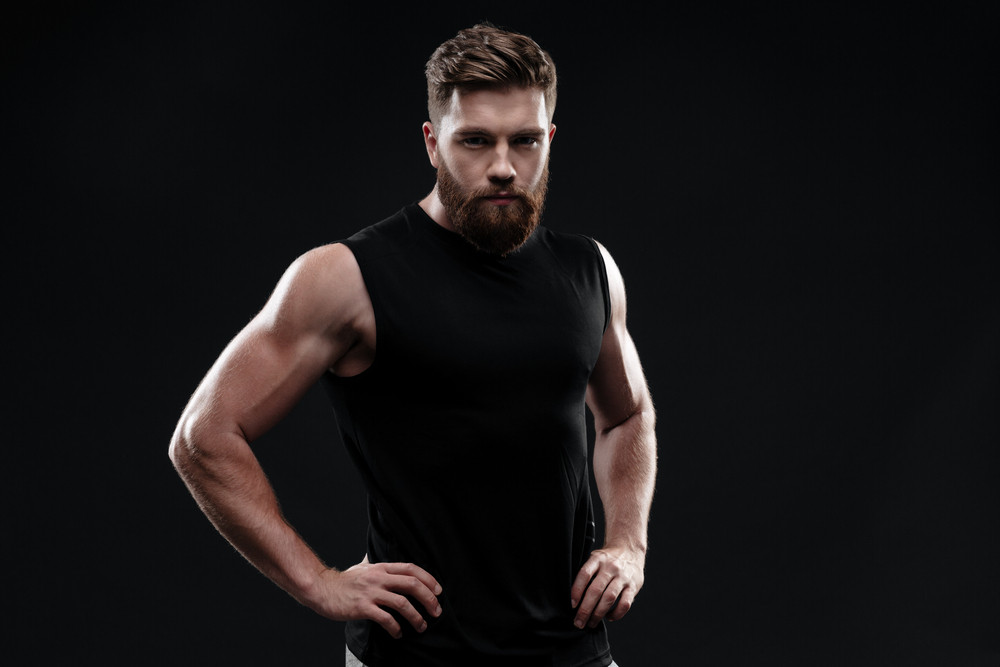 Athletic man in studio. looking at camera. arms at hips. isolated dark background