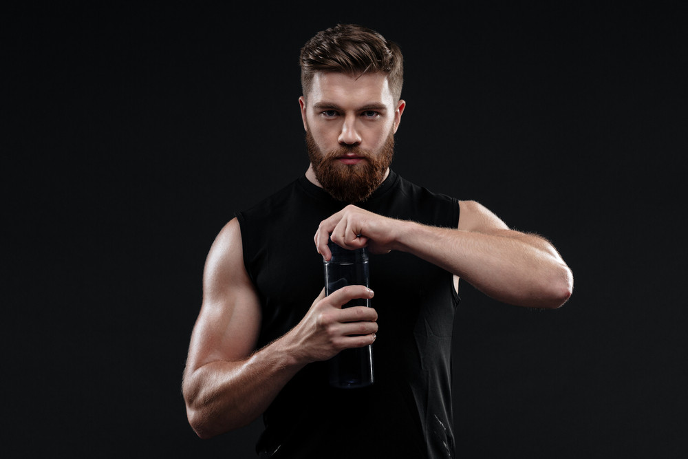 Athletic man with bottle. so serious. looking at camera