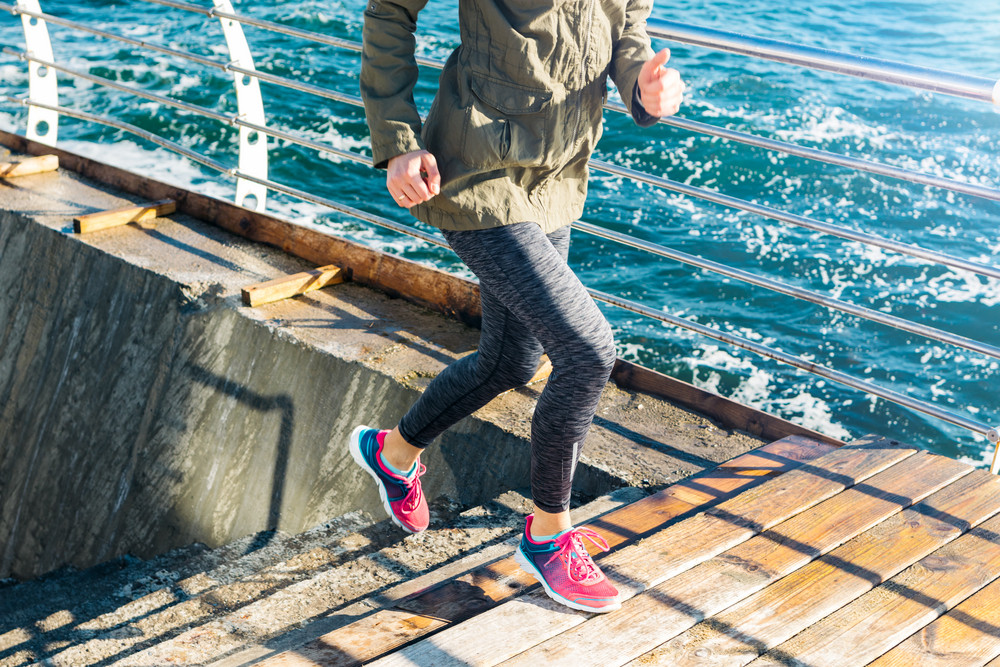 Athletic woman in sports clothes runs up the stairs in sneakers against the background of the sea. Sunny morning, a healthy lifestyle outdoors.