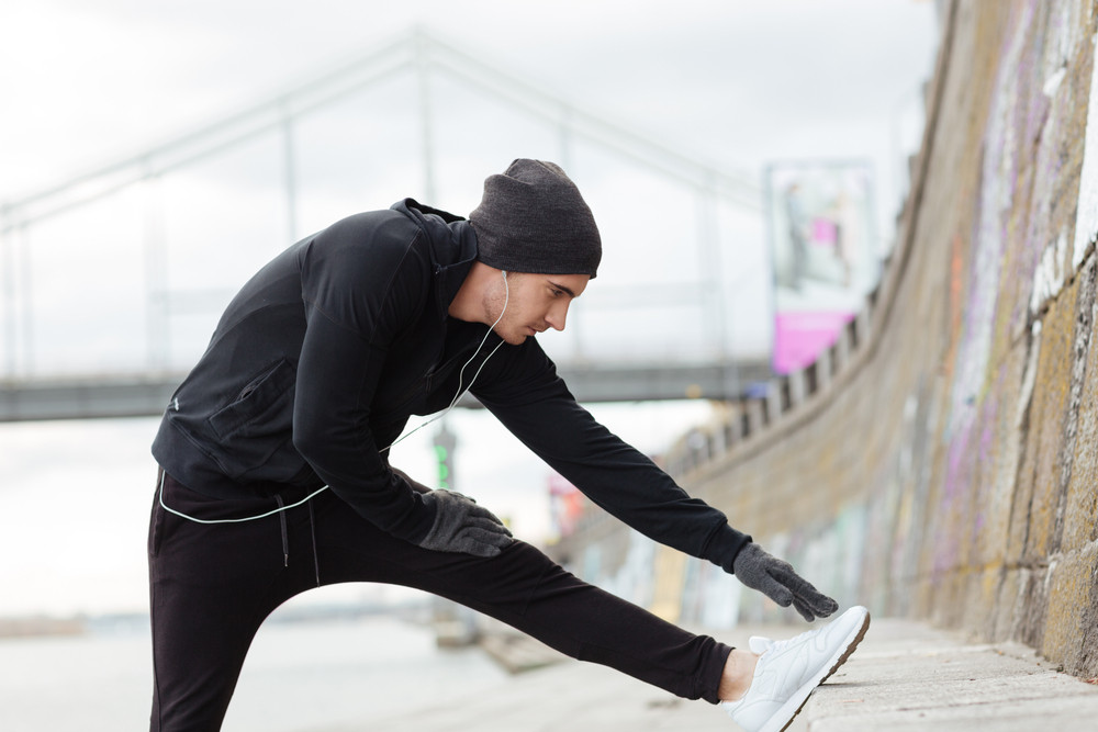Athletic young man listening to music and stretching legs outdoors