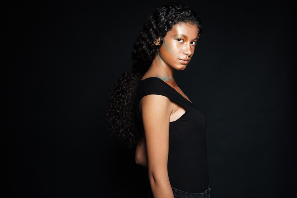 Attractive african american young woman with curly long hair and fashion makeup over black background