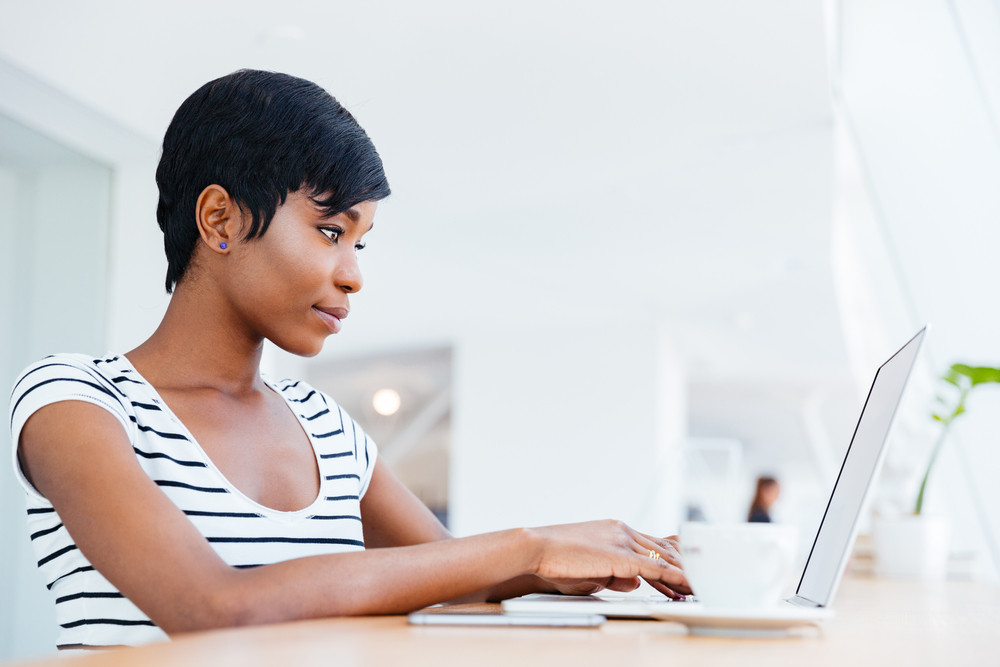 Attractive african businesswoman working with laptop and drinking coffee in office