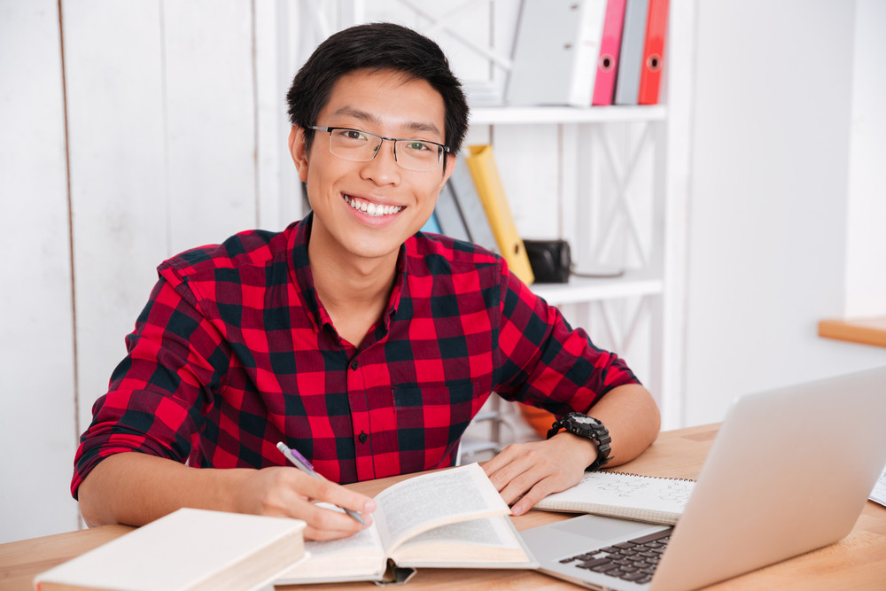 Attractive asian student looking at camera and writing notes while reading a books and working on laptop in classroom.