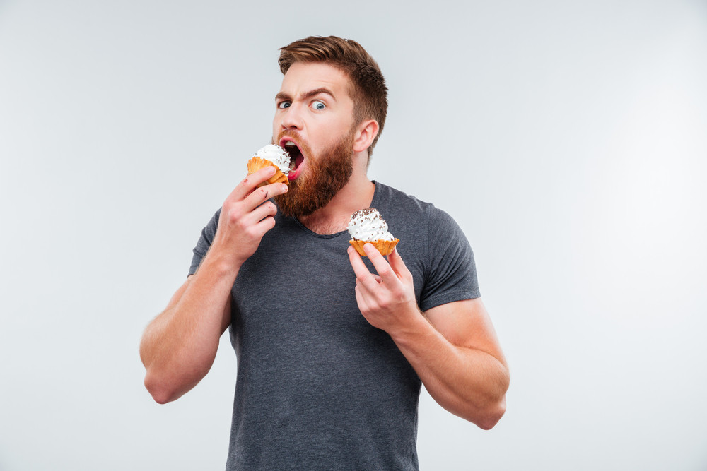 Attractive bearded man biting cream cake isolated on white background