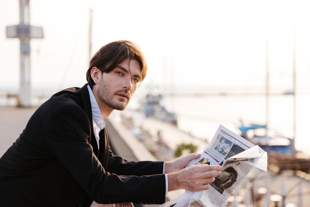 Attractive businessman reading newspaper in port of Odessa