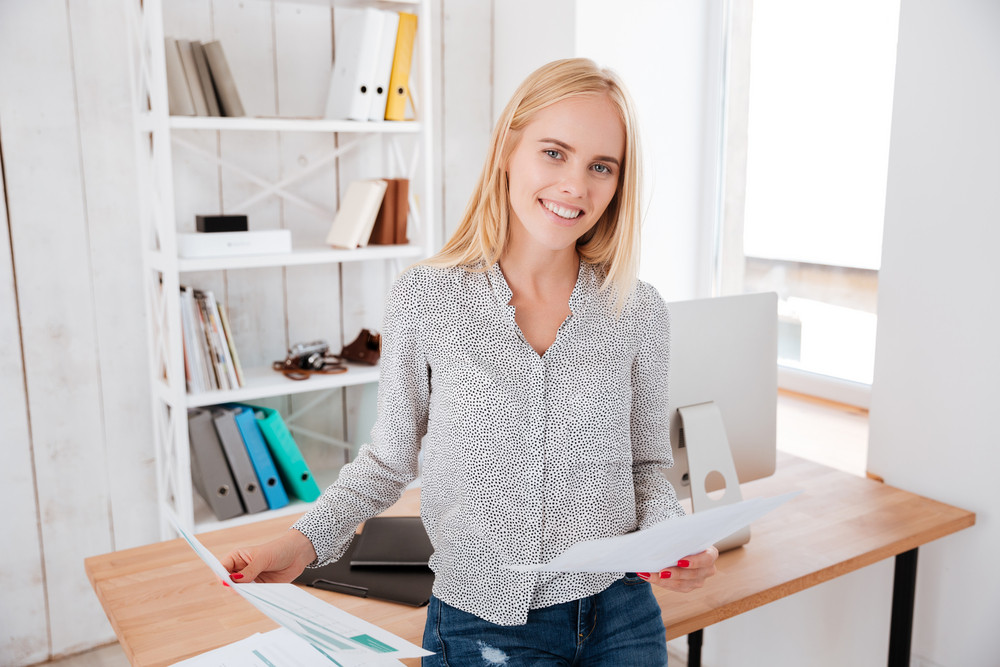Attractive casual businesswoman holding documents and sitting on the office desk