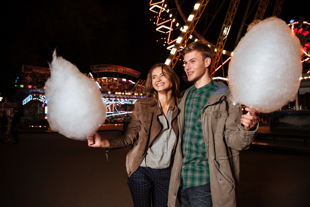 Attractive couple in amusement park with cotton candy. in warm clothes