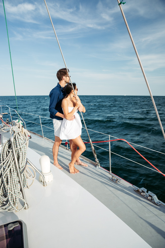 Attractive couple standing together on a yacht enjoy bright sunny day on vacation