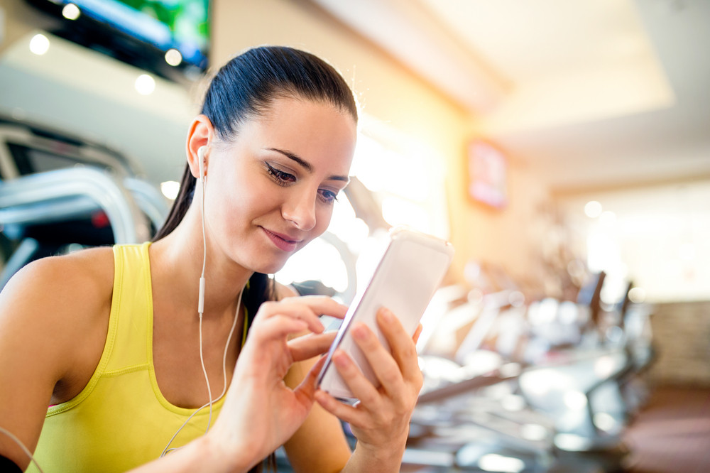 Attractive fit woman in a gym with smart phone against a row of treadmills