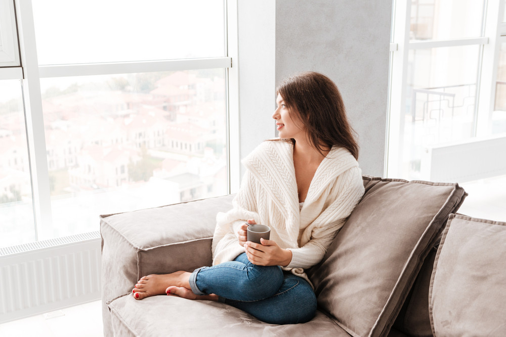 Attractive peaceful young woman with cup of coffee sitting and dreaming on sofa at home