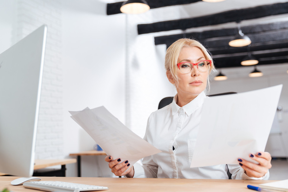Attractive pensive mature businesswoman reading papers in office