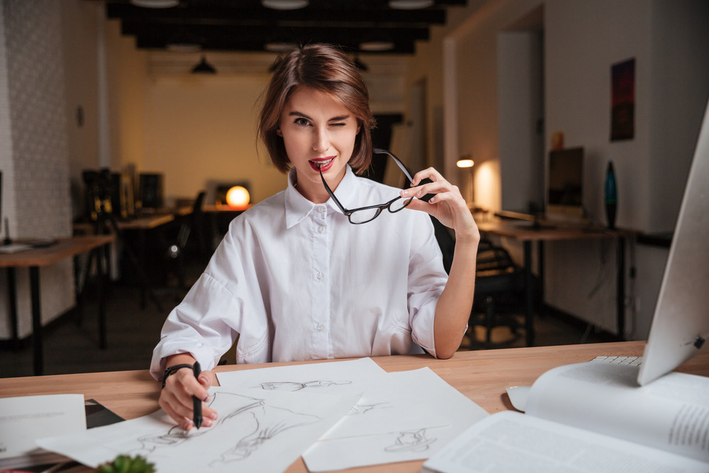 Attractive playful young woman fashion designer holding glasses and winking in office