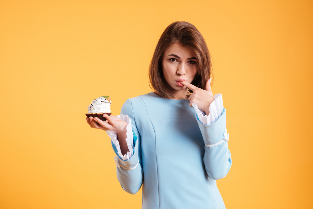 Attractive seductive young woman licking her finger and holding cupcake over yellow background