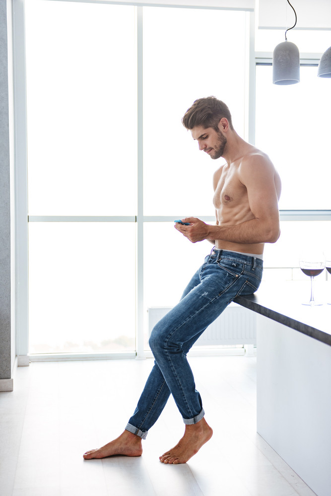 Attractive shirtless young man standing and using cell phone at home