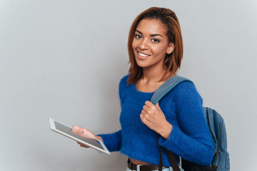 Attractive smiling african woman in sweater standing sideways with tablet computer in hand and with backpack on shoulder
