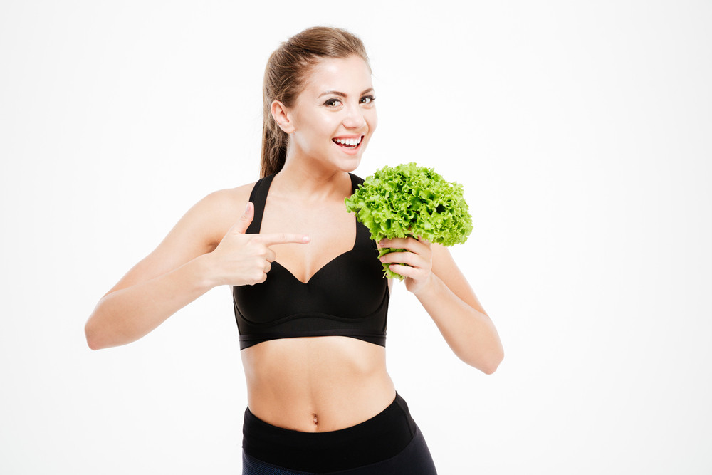 Attractive smiling fitness woman pointing finger at lettuce leaves isolated on a white background