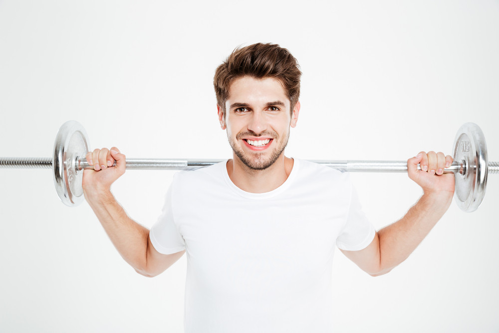 Attractive smiling sportsman standing and holding barbell over white background