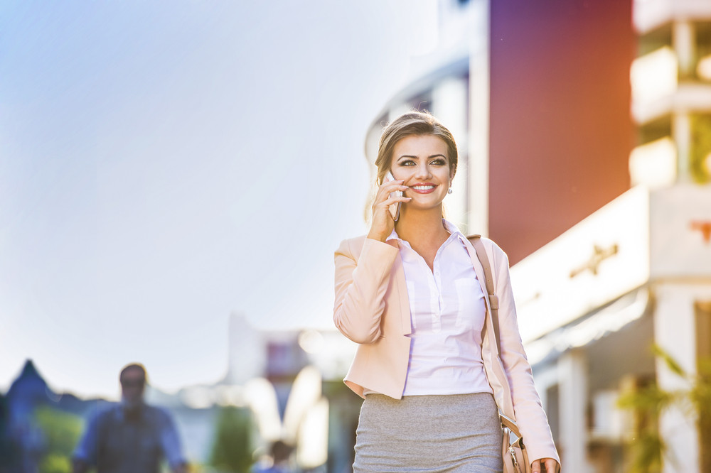 Attractive young business woman walking in the city