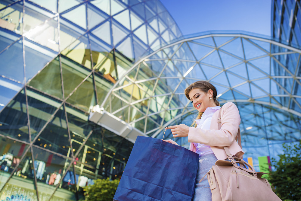 Attractive young business woman with shopping bags in front of the mall