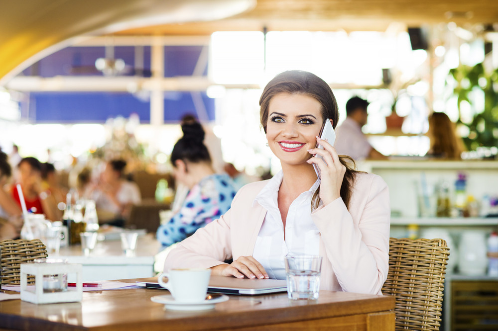Attractive young businesswoman with smartphone in cafe