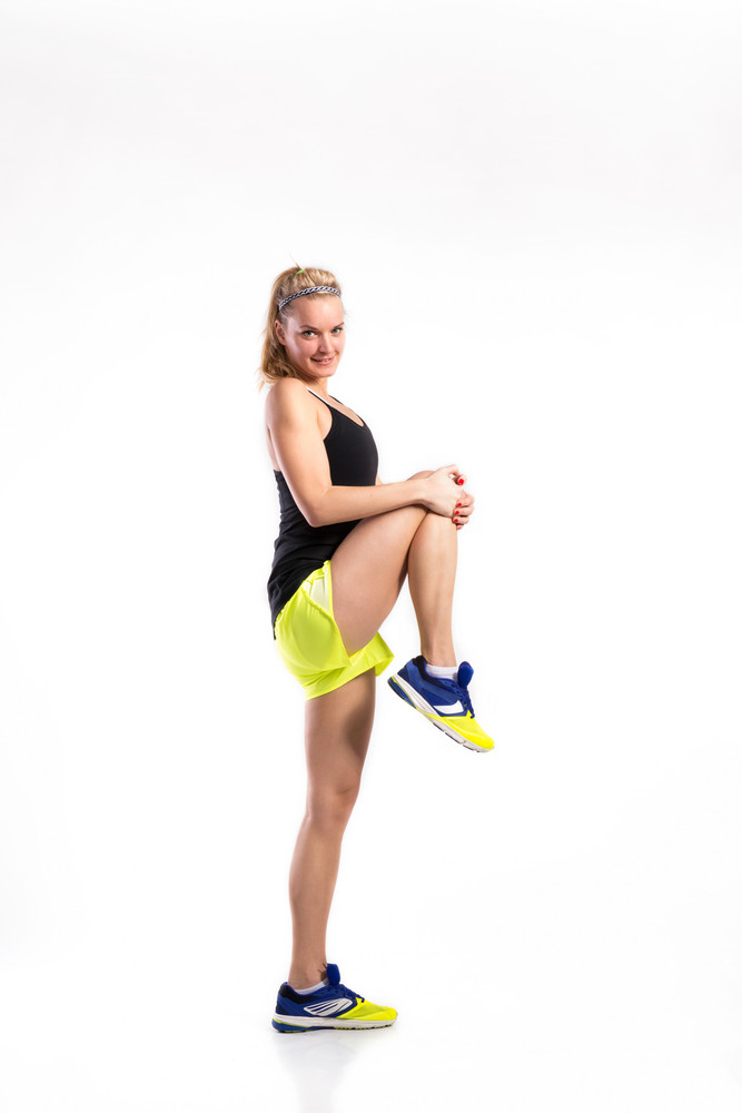 Attractive young fitness woman in black singlet and yellow shorts, stretching her legs. Studio shot on gray background.