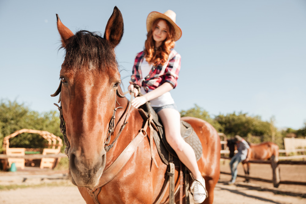 Attractive young redhead cowgirl in hat riding her horse at ranch