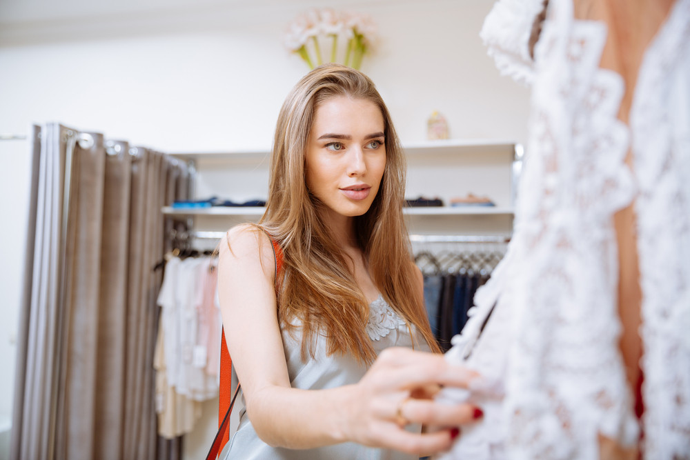 Attractive young woman doing shopping and choosing clothes in clothing store