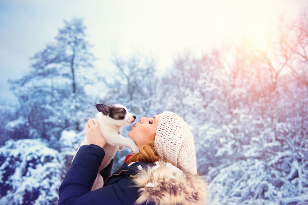 Attractive young woman having fun outside in snow with her dog puppy