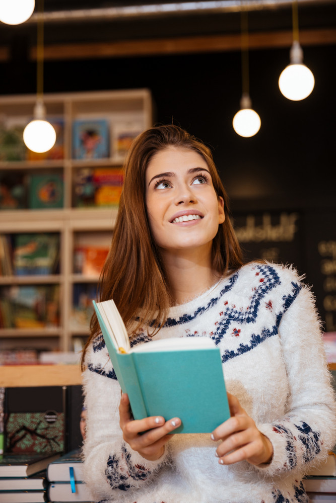 Attractive young woman holding open book ad looking up while sitting in library