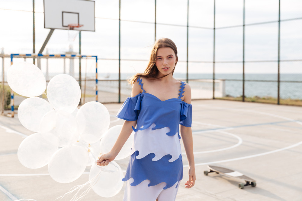 Attractive young woman in stylish dress standing and holding balloons on outdoor sports ground