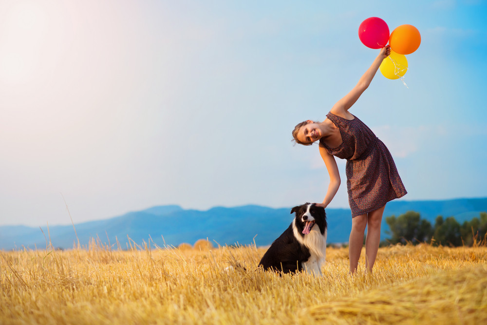 Attractive young woman outside in a field holding a dog and baloons.