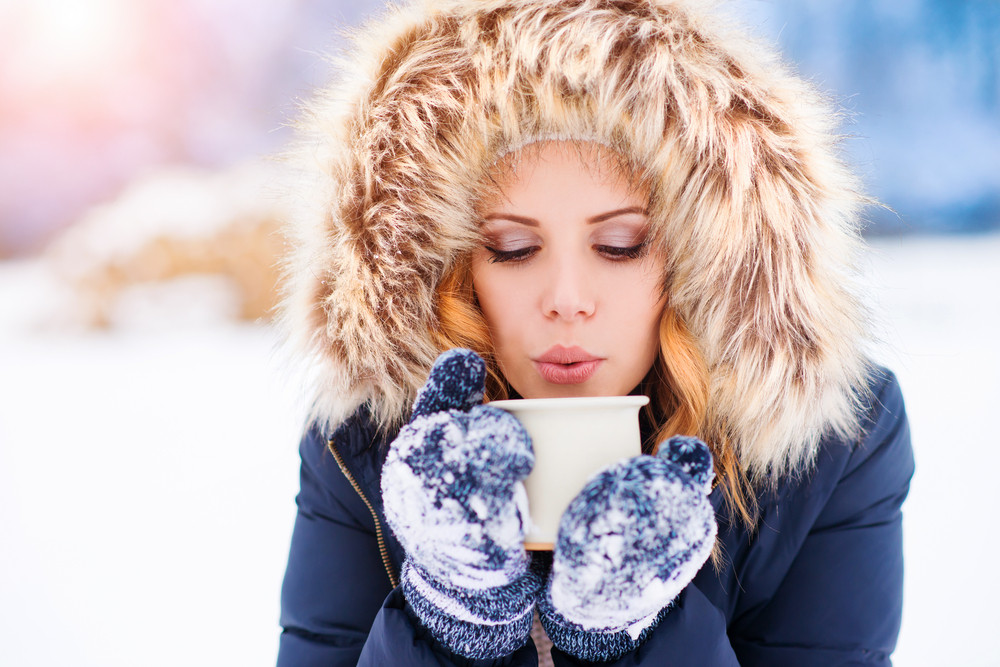 Attractive young woman outside in snow with a cup of coffee