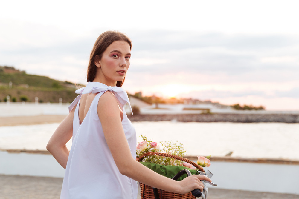Attractive young woman with bicycle standing on promenade
