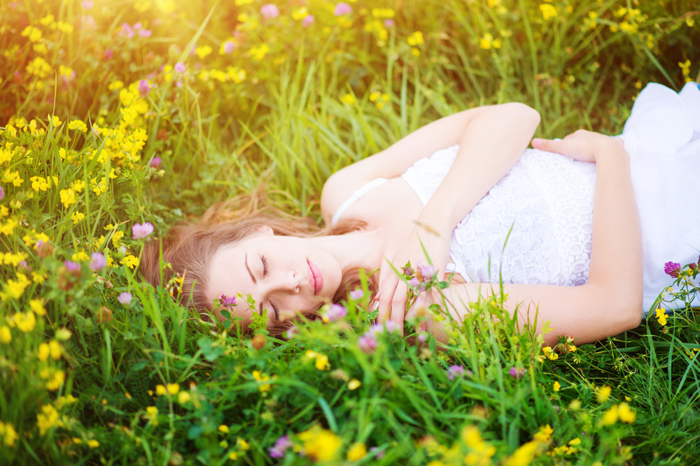 Attractive young woman with flowers outside on a meadow full of flowers.